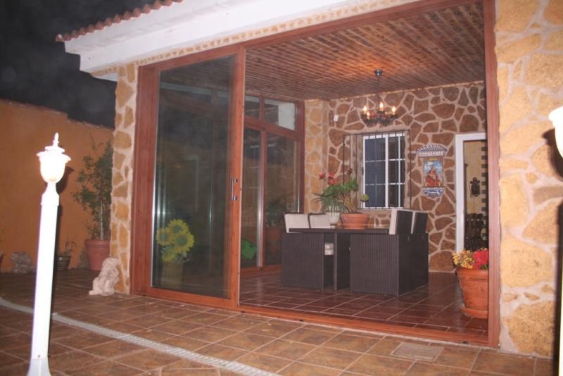 Porche de piedra, madera y aluminio imitando madera